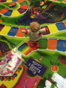 Diverse dolls act as game pieces on out giant candy land board.